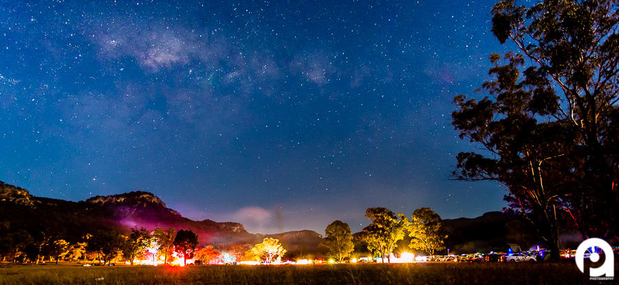 Psyfari Festival, with the Milky Way stretching overhead, lights and dust rising from the ground.