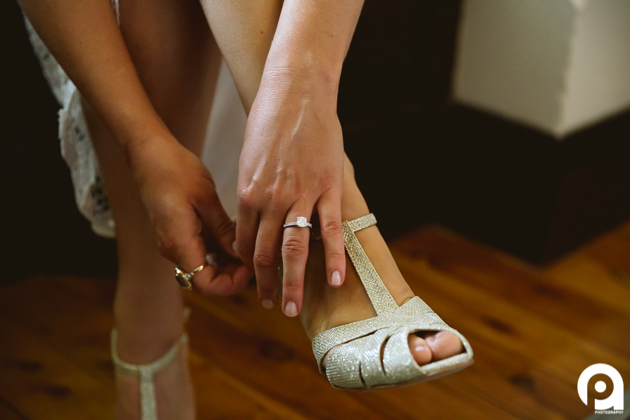 A beautiful detail shot of Sarah putting her shoes on and her engagement ring.