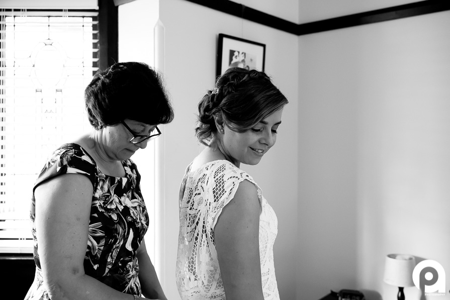 Sarah's mother helps her put on her handmade wedding gown.