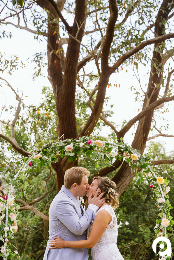 The first kiss with a backdrop of flowers & tress.